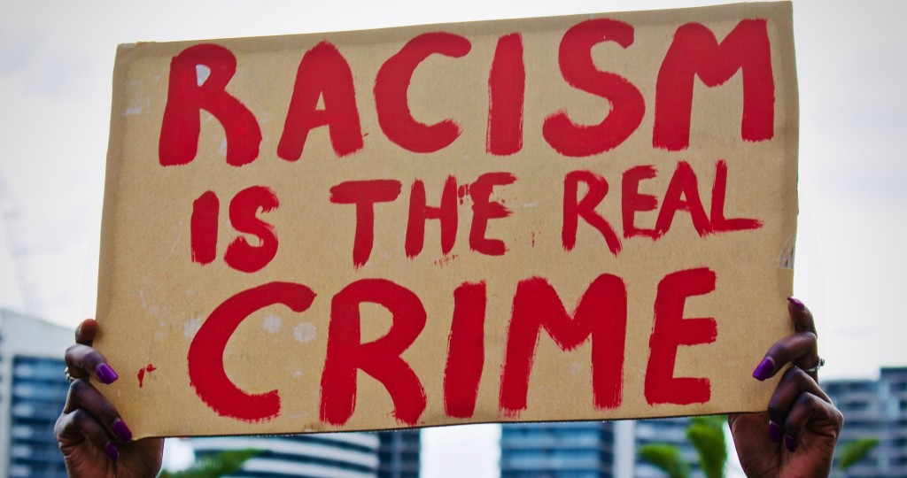 "A placard that reads ""Racism is the real crime""  By Charandev Singh"